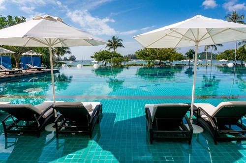 Hotelpool mit Liegen im Wasser und blauem Himmel